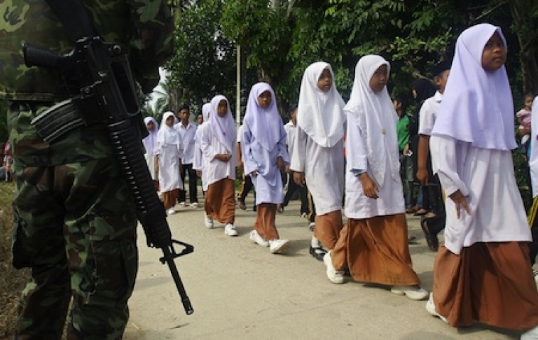 <p>School-aged children guarded by Thai troops in Narathiwat province. Nearly 5,000 have died in an Islamic insurgency waged to restore a sultanate absorbed by Thailand (then Siam) around the dawn of the 20th century.</p>