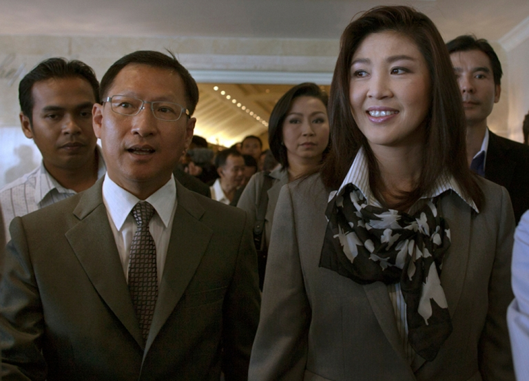 <p>Yingluck Shinawatra is flanked by party members after a news meeting July 4th, 2011 in Bangkok, where she announced her Pheu Thai party would form a coalition with four smaller parties.</p>