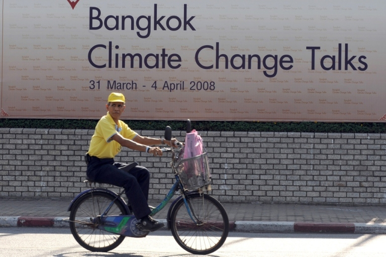 <p>A man rides past by a banner in front of the United Nations building in Bangkok on March 30, 2008, on the eve of an earlier U.N. climate warming conference.</p>