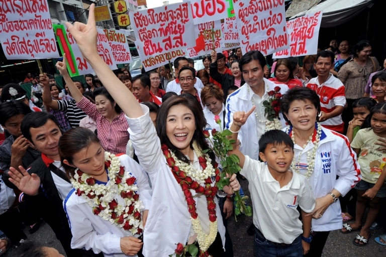 <p>Yingluck Shinawatra, sister of fugitive Thai ex-prime minister Thaksin Shinawatra, greets her supporters during her election campaign at a market in Chiang Mai on May 21, 2011.</p>