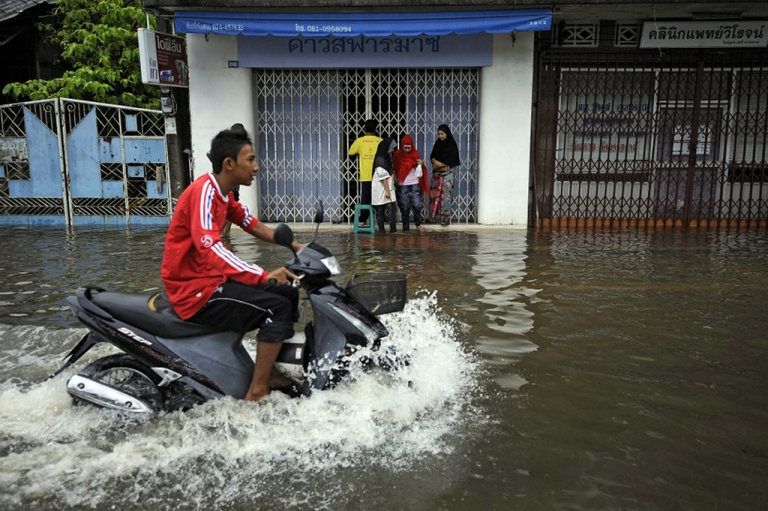 <p>A Thai man rides his motorbike down a flooded street following heavy rains in Thailand's southern city of Narathiwat on March 29, 2011.</p>