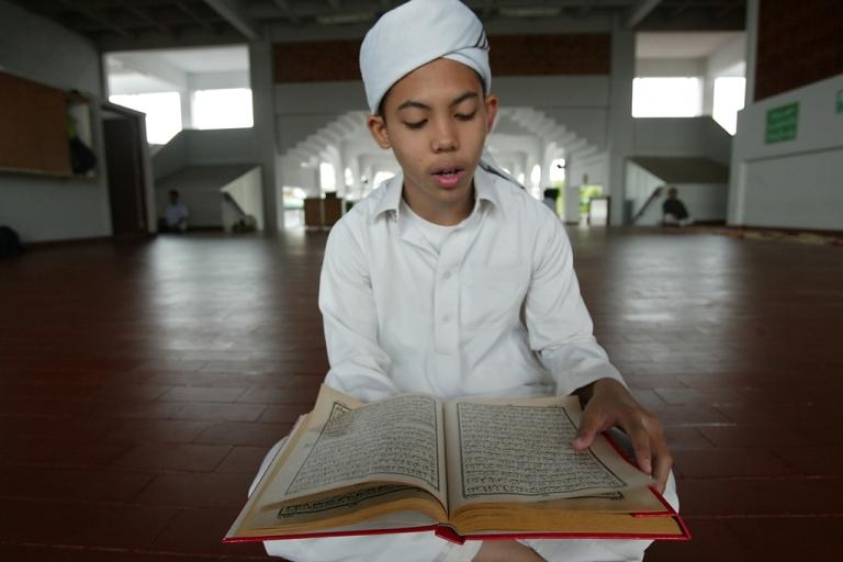 <p>A Thai Muslim boy reads the Quran.</p>