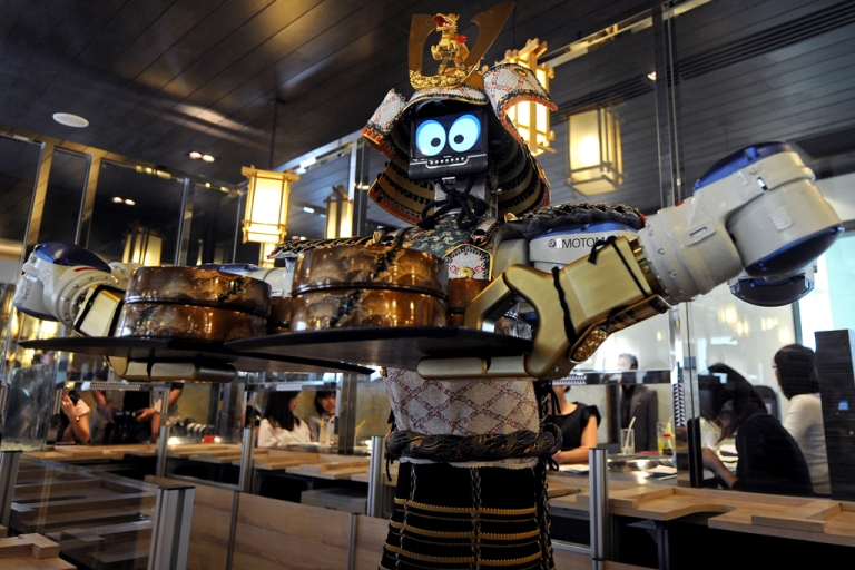 <p>A robot waiter holds a tray of food at a Japanese robot restaurant in Bangkok on April 1, 2010.</p>
