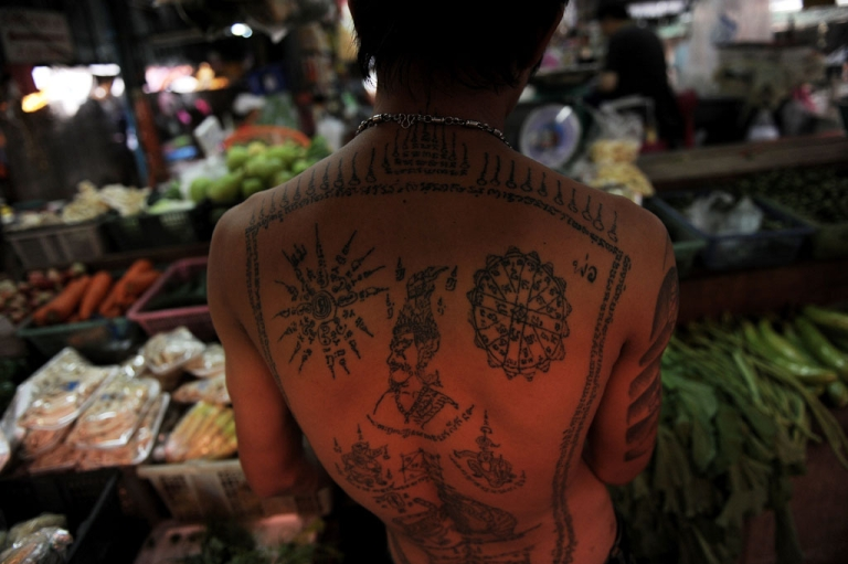 <p>A Thai stall employee with a tattooed back arranges vegetables at a market in downtown Bangkok on March 9, 2011.</p>