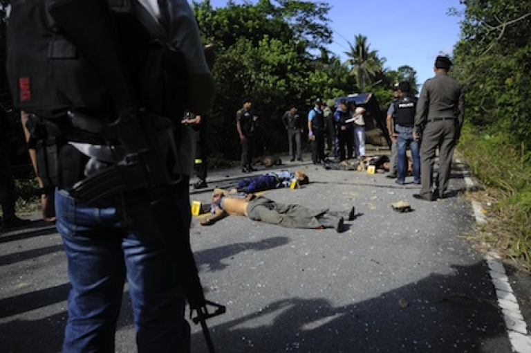 <p>Thai police officers inspect the bodies of six Thai Buddhist hunters, shot dead by suspected separatist Muslim militants following a roadside bomb blast in Thailand's restive southern province of Narathiwat on November 2, 2011.</p>