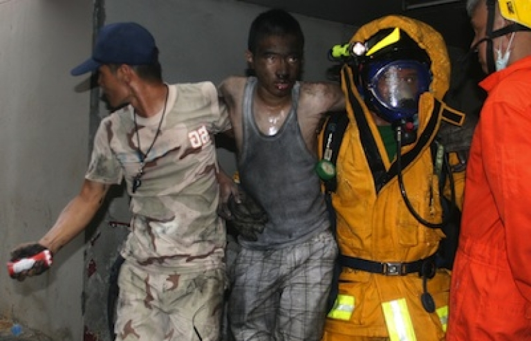 <p>Thai firemen carry an injured man after a fire at the Lee Gardens Hotel in downtown Hat Yai, Thailand on March 31, 2012.</p>