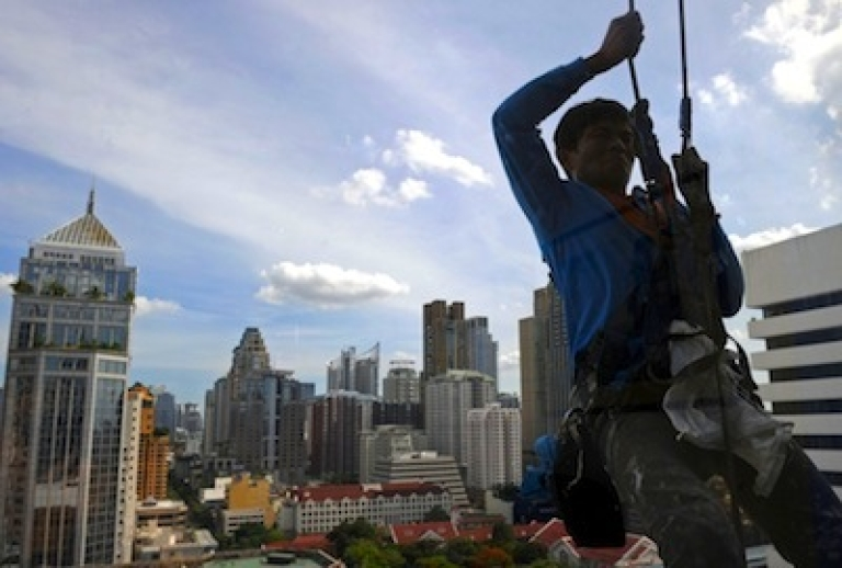 <p>A Thai worker hangs from a cable while he cleans a building's windows in Bangkok on June 9, 2011.</p>