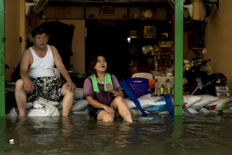 <p>Local residents sit on sandbags in front of their shop surrounded by flood waters after a mud and sandbag wall collapsed in Bang Bua Thong in Nonthaburi province, suburban Bangkok, on Oct. 19, 2011.</p>