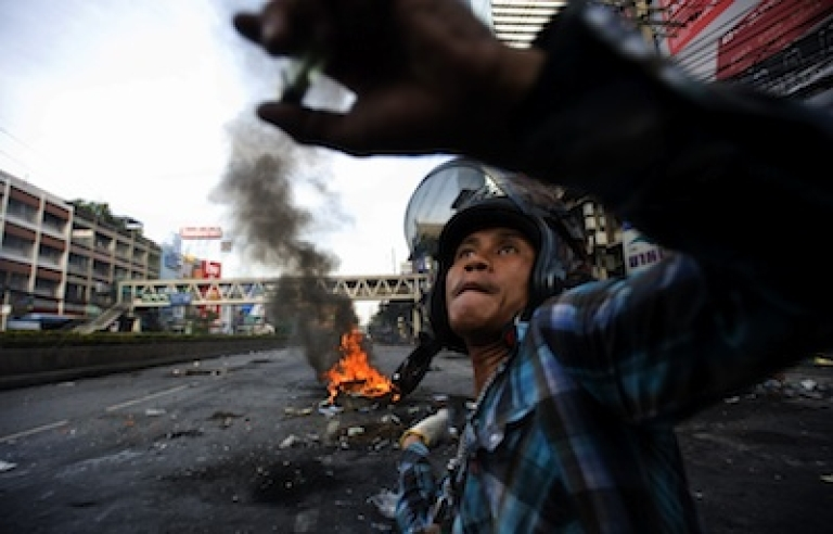 <p>A Thai anti-government red shirt protester hurls a large firecracker over a barricade during clashes on May 18, 2010 in Bangkok, Thailand.</p>