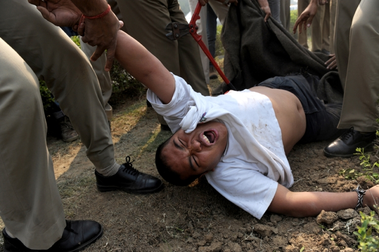 <p>A lone protester is dragged away by Indian police moments after he tried to set himself on fire in front of the Chinese embassy in New Delhi on Nov. 4, 2011.</p>