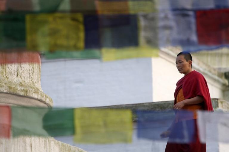 <p>A Tibetan Buddhist nun looks through a line of prayer flags at the Boudhanath Stupa in Kathmandu on October 5, 2009.</p>