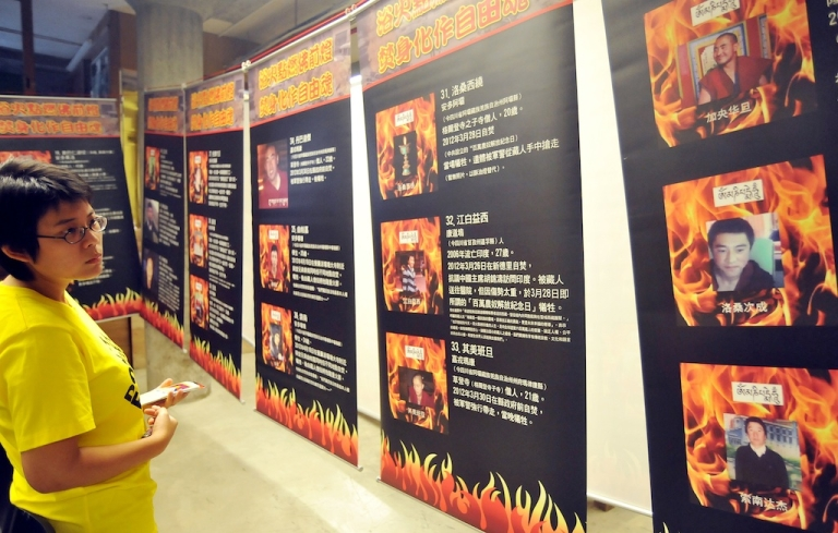 <p>A woman attends an Amnesty International exhibition in Taipei on June 29, 2012 showing portraits of reported self-immolation victims in Tibetan-inhabited areas of China.</p>