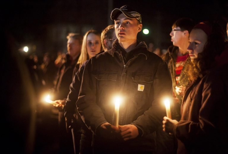 <p>Students and those in the community embrace one another on Tuesday as they hold a candlelight vigil at St Mary's of the Assumption Church in Chardon, Ohio.</p>