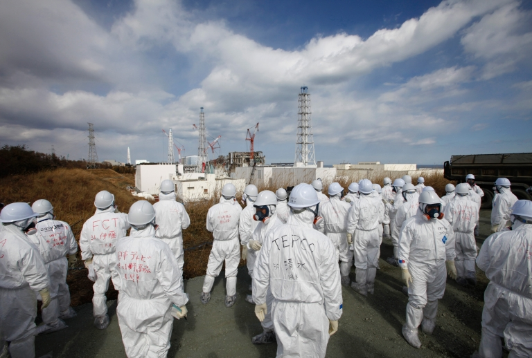 <p>Members of the media wearing protective suits and masks are escorted at the Tokyo Electric Power Company's tsunami-crippled Fukushima Daiichi nuclear power plant on Feb 20.</p>