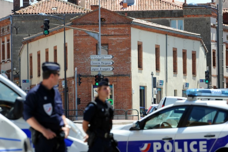 <p>Police stand outside the CIC bank in Toulouse, in the south of France, where four people have been taken hostage by a man claiming to belong to Al Qaeda.</p>