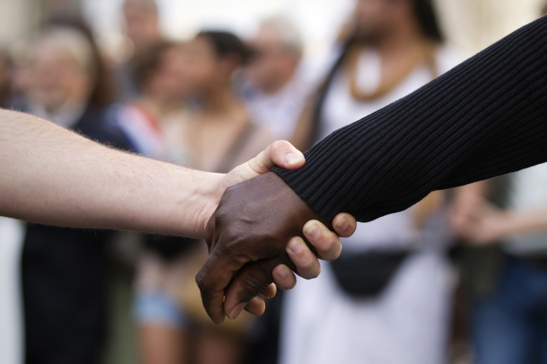 <p>A white person and a black person hold hands as they take part in a march in Paris today. The march was called by human rights organizations following the serial murders in the Midi-Pyrénées region this month in which an Islamic extremist, since killed, was the suspected culprit.</p>