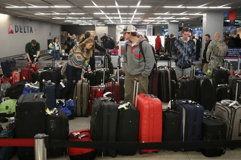 <p>Passengers arriving at O'Hare International Airport search for their luggage on Dec. 21, 2012, in Chicago, Ill. Trakdot, one of the many gadgets from this year's Consumer Electronics Show, helps alleviate travel stress by texting passengers when their bags have arrived.</p>