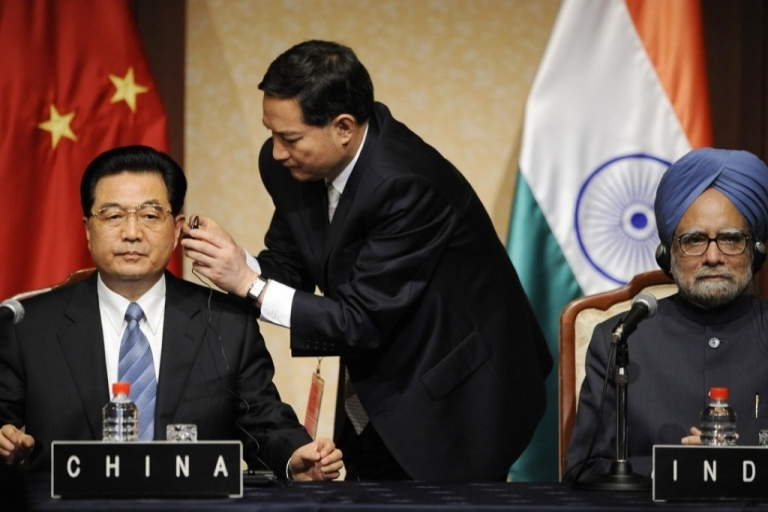 <p>Chinese President Hu Jintao is helped by an aide to set up a headphone for translation as Indian Prime Minister Manmohan Singh looks on. If a consortium of Asian nations have their way, machine translation will someday take the place of human translators.</p>