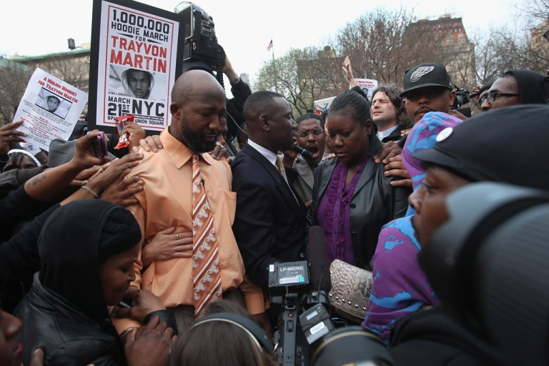 <p>Tracy Martin (left in orange shirt), and Sybrina Fulton,(R), parents of slain teenager Trayvon Martin, pray at a Million Hoodies March on March 21, 2012 in New York City. The family members joined hundreds of protesters calling for justice in the killing of Trayvon Martin, 17, who was was pursued and shot on February 26 in Sanford, Florida by