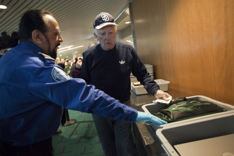 <p>Transportation Security Administration (TSA) officer Stephen Candia helps a patron pass though a security check. Several current and former TSA agents at LAX have been indicted for allegedly taking bribes to allow drug shipments through security.</p>