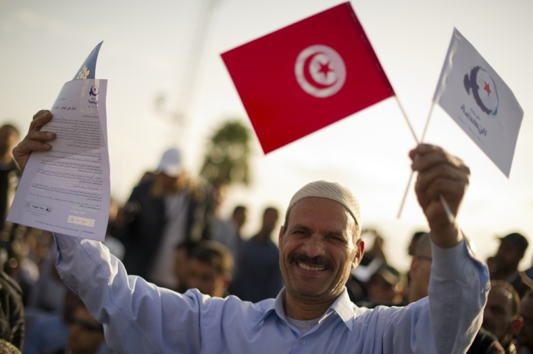 <p>A Tunisian man waves flags before elections on Oct, 21, 2011.</p>