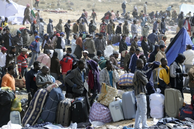 <p>Refugees line up in a field covered with garbage as they wait to get on a bus to the Jerba airport at the Tunisian transit camp of Choucha on March 16, 2011. The United Nations said on March 10 that more than 250,000 people had fled Libya to neighboring countries since the revolt against Muammar Gaddafi started in mid-February.</p>