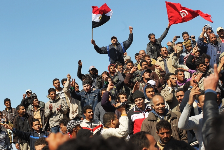<p>Waving Egyptian and Tunisian flags, migrant workers who recently fled into Tunisia from Libya demand to be taken home during a demonstration at a displacement camp on Feb. 27, 2011 in Ras Jdir, Tunisia. As fighting continues in and around the Libyan capital of Tripoli, tens of thousands of guest workers from Egypt, Tunisia and other countries are fleeing to the border of Tunisia to escape the violence. The situation is quickly turning into a humanitarian emergency as fledgling Tunisia is overwhelmed with the migrant workers. Libyan leader Muammar Gaddafi has vowed to fight to the end.</p>