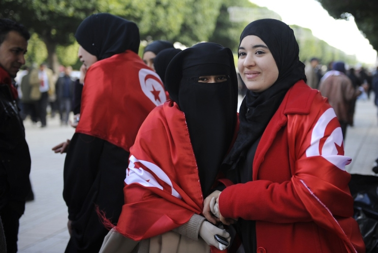 <p>Tunisian women wrapped in Tunisian flags pose during a demonstration to demand jobs and dignity as the north African country marks a year to the day since its despot Zine El Abidine Ben Ali fled into exile on January 14, 2012 on Habib Bourguiba Avenue in Tunis. Some demonstrators, wearing the red and white of the national flag, called for recognition of the 'martyrs' killed during the weeks of unrest before Ben Ali was toppled.</p>