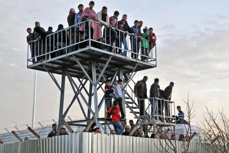 <p>Syrian refugees in Turkey watch the border from Oncupinar Refugee Camp on April 9, 2012.</p>
