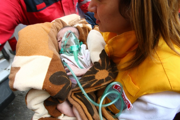 <p>Rescue workers carry Azra Karaduman, a two-week-old baby who was pulled from the debris of the earthquake on October 25, 2011 in Ercis.</p>