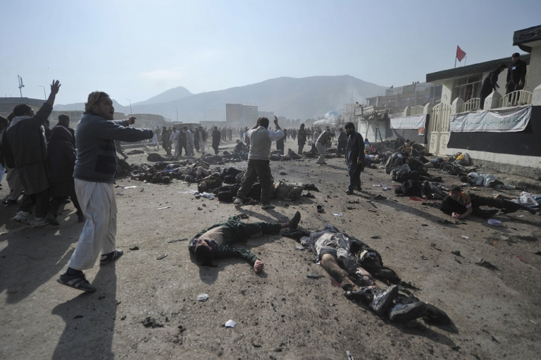 <p>Afghan men cry as they try remove the bodies and help wounded people after explosions during a religious ceremony in the centre of Kabul on December 6, 2011.</p>