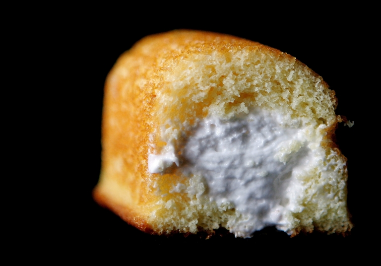<p>A Hostess Twinkie golden sponge cake with its creamy filling exposed.</p>