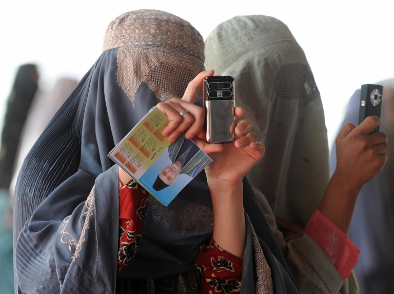 <p>Burqa clad Afghan women taking pictures on their mobile phones during the 2009 presidential election campaign. Photo taken on 17 August 2009.</p>