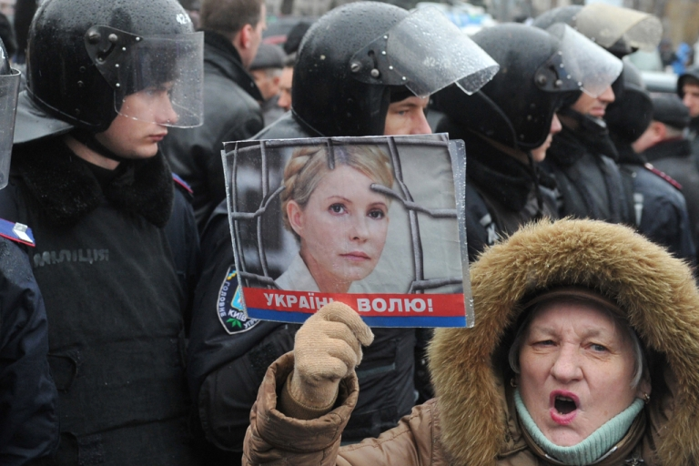 <p>A supporter of Ukraine's former Prime Minister Yulia Tymoshenko holds a picture of the opposition leader during a rally held outside Kiev's courthouse on December 20, 2011. The European Union warned Ukraine on December 19 that the jailing of ex-prime minister Yulia Tymoshenko had stalled the signing of an agreement taking Kiev a step closer to membership of the bloc. AFP PHOTO/ SERGEI SUPINSKY</p>