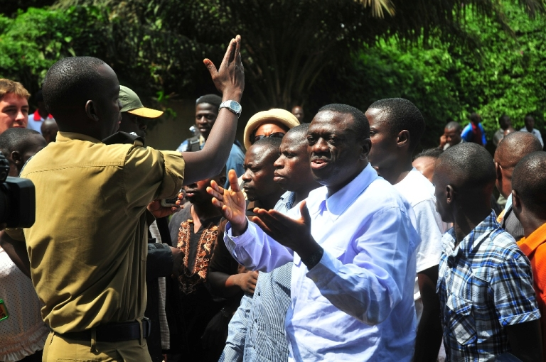 <p>Uganda main opposition leader, President of the Forum For Democratic Change (FDC), Kizza Besigye (R) argues with a policeman, a few minutes before being arrested with members of Action for Change (A4C) on Jan. 19, 2012 in Kampala. The opposition politicians were planning to hold a rally at Katwe grounds in Kampala as part of third-round of walk-to-work protesting high cost of living. Former presidential challenger Besigye has been repeatedly arrested and arraigned in court since launching protests last year against the rising cost of living.</p>