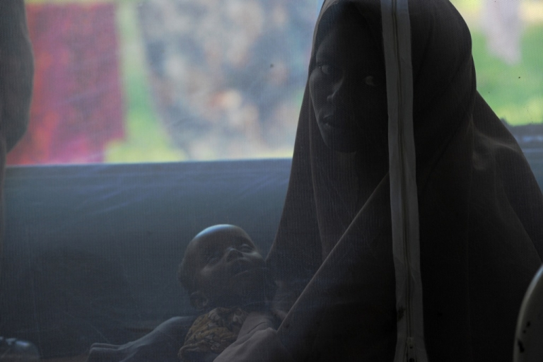 <p>A mother holds her seven-month-old daughter underneath a mosquito tent while at the hospital on August 16, 2011.</p>