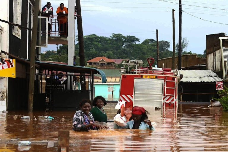<p>Littering contributes to flood disasters. Here, Ugandan residents cross a flooded street on the road to Entebbe in the Namasuba neighborhood in Kampala after a heavy downpour earlier in the day. Heavy rains pounded the Ugandan capital early November 16, 2007 flooding homes and submerging vehicles only weeks after the region suffered the worst floods in decades.</p>