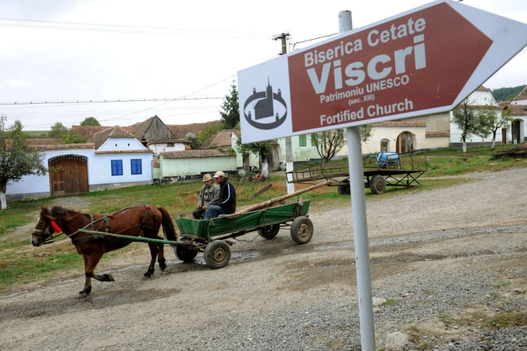 <p>Men ride a carriage in Viscri, Romania, on Oct. 8, 2010. More than 11,000 tourists from around the world came in 2009 to see Viscri's pastel-coloured houses and its UNESCO World Heritage fortified church.</p>