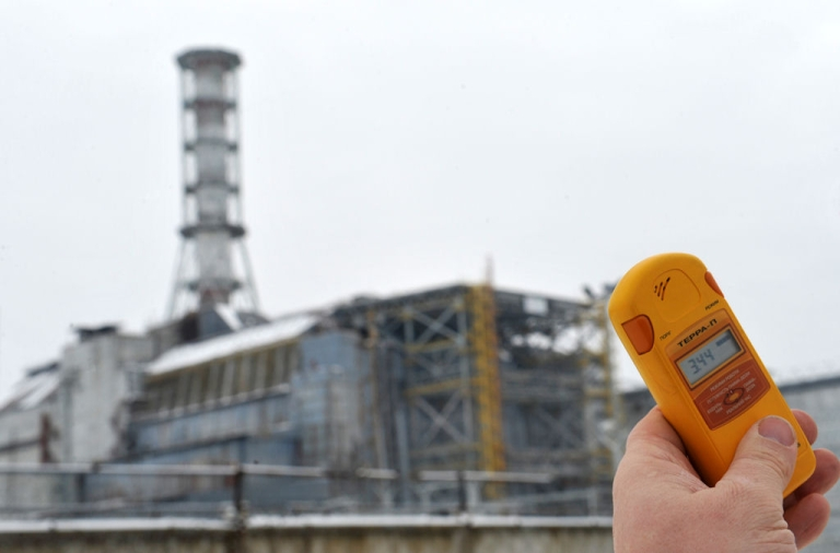 <p>A man holds a geiger counter in front of the sarcophagus covering the destroyed fourth block of the Chernobyl nuclear power plant on Feb. 24, 2011 ahead of the 25th anniversary of the meltdown of reactor number four due to be marked on April 26, 2011.</p>