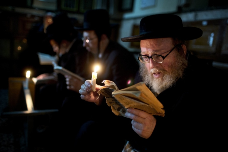 <p>Ultra-Orthodox Jewish men use a candle light to read from the book of Eicha (Book of Lamentations) during the annual Tisha B'Av (Ninth of Av) fasting and a memorial day, commemorating the destruction of ancient Jerusalem temples, in the ultra-Orthodox neighborhood of Mea Shearim in Jerusalem, on July 28, 2012.</p>