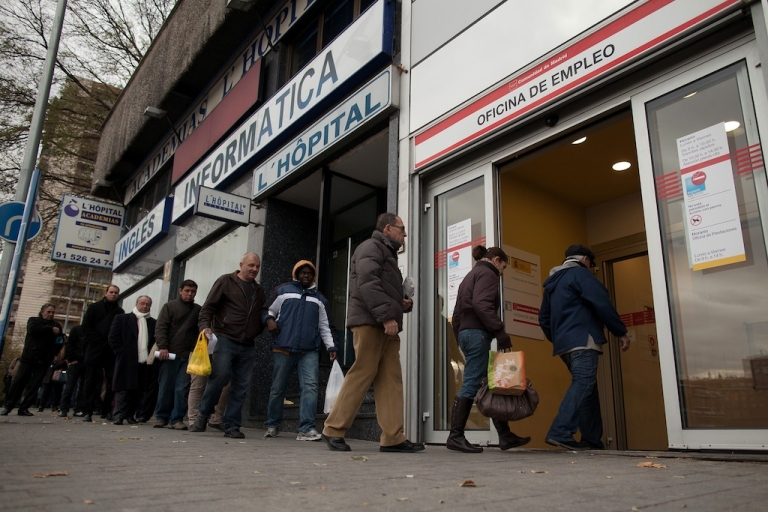 <p>People queue to enter a government employment office in Madrid on December 4, 2012.</p>