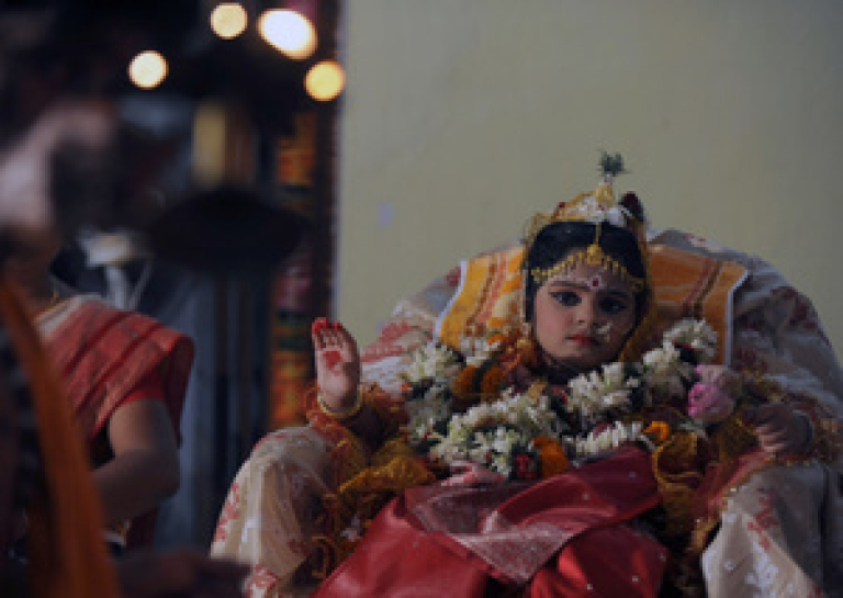 <p>A young Indian Hindu unmarried girl, known as a 'kumari', is dressed as the Hindu goddess Durga during a ritual for the Durga Puja festival in Siliguri on October 4, 2011.</p>
