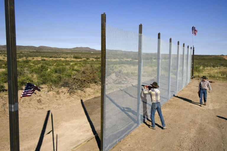 <p>This picture taken on October 20, 2006, shows workers building a 14-foot high mesh fence along the US-Mexican border near Naco, Arizona.</p>
