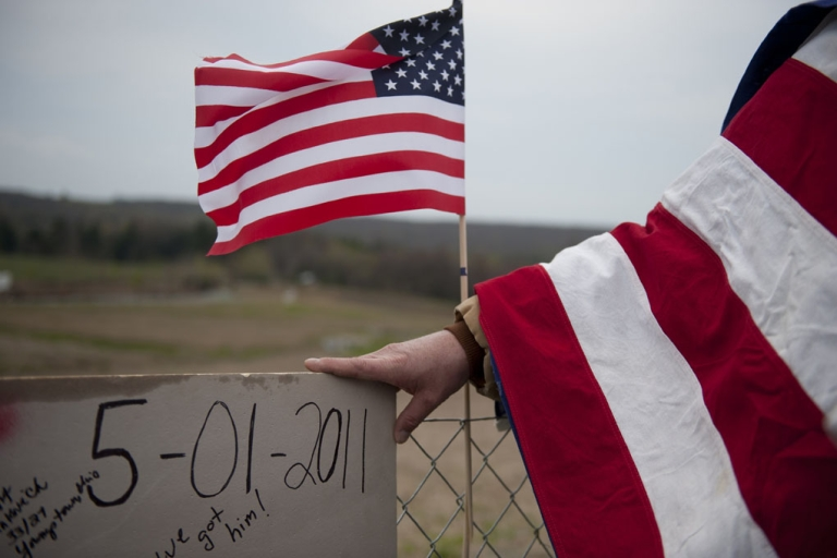 <p>Jeff Ray, of Shanksville, Pa., holds a homemade sign and looks over the crash site of Flight 93 following the announcement that Osama Bin Laden had been killed. Nearly 10 years after September 11, 2001, construction is underway to erect a formal memorial at the crash site.</p>
