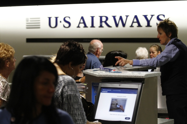 <p>Travelers check-in at the US Airways ticket counter on April 19, 2012.</p>