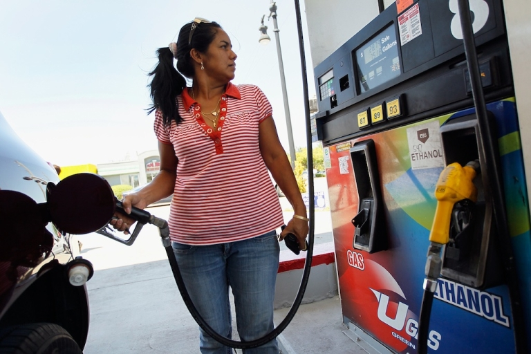 <p>Carlin Malina pumps gas into her vehicle at a Ugas station on April 24, 2012, in Miami, Fla.</p>