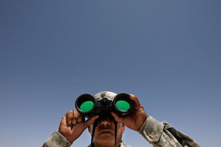 <p>A National Guard specialist spots three men near the U.S.-Mexico border near Sunland Park, New Mexico, on June 26, 2007.</p>