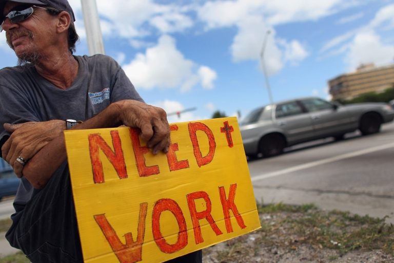 <p>Stephen Greene works a street corner hoping to land a job as a laborer or carpenter on June 3, 2011 in Pompano Beach, Florida.</p>
