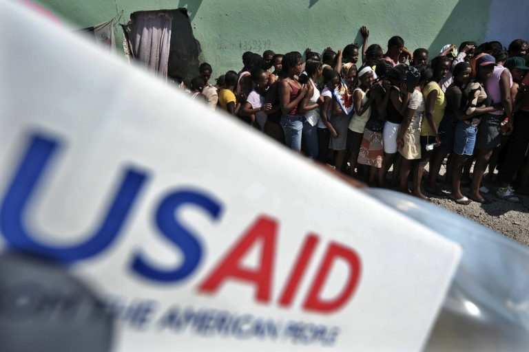 <p>People line up to receive items at a USAID distribution point in Port-au-Prince following the massive 7.0-magnitude quake that shattered Haiti. However, many believe the West's pattern of unfettered aid is actually contributing to the problem of dependence and making development impossible.</p>