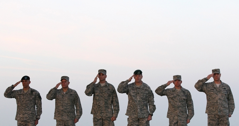 <p>US military oficers salute during a dignified transfer fat Dover Air Force Base.</p>